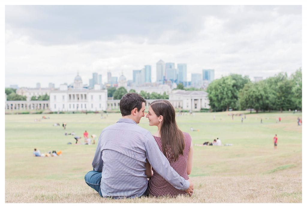 Engaged couple in Greenwich Park with London skyline