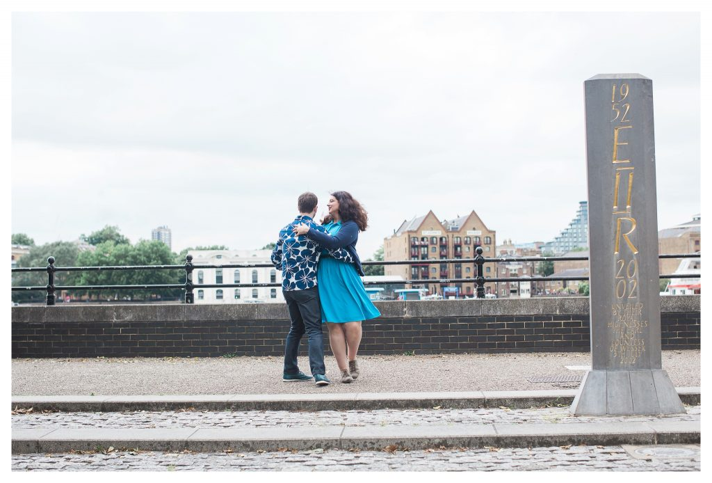 Engaged couple dancing along the Thames Path on London riverside