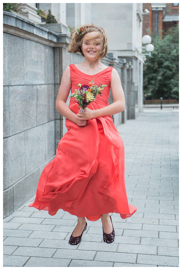 Flower girl jumping in coral dress