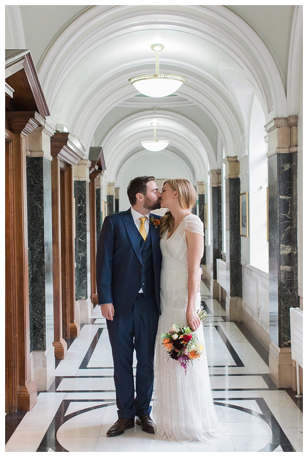 Bride and groom posing inside Islington town hall