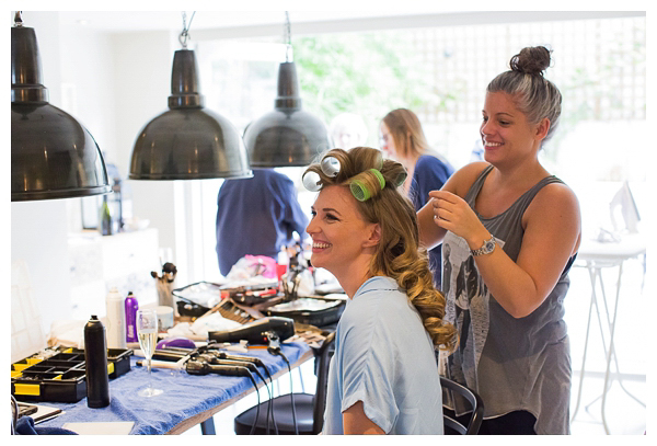 bride getting hair done on wedding morning