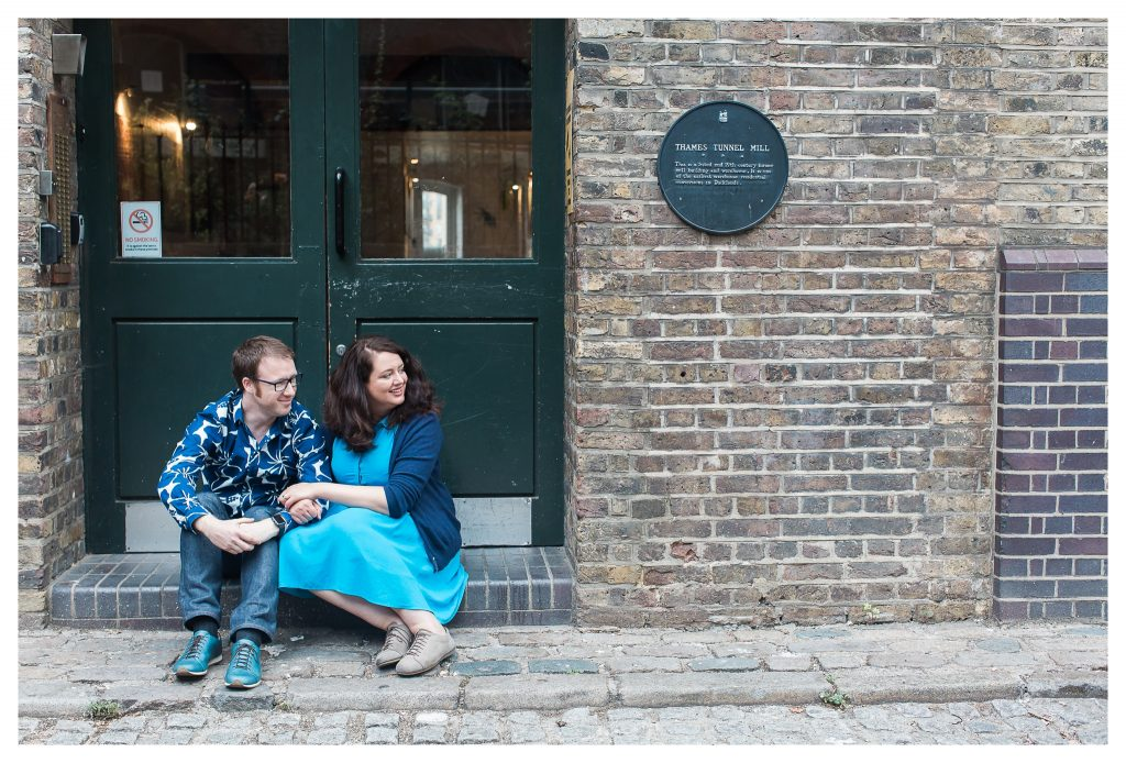 Engaged couple sitting in doorway in Rotherhithe