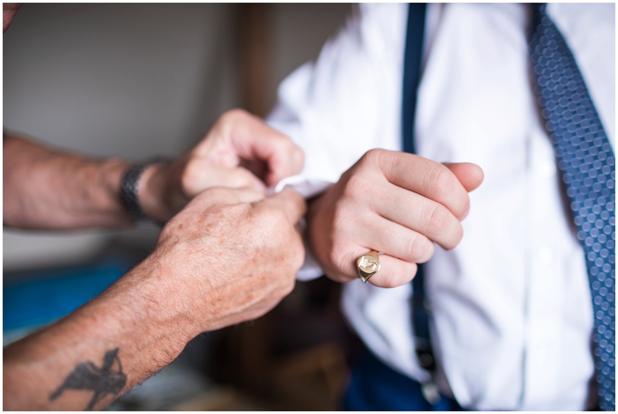 Grooms dad putting son's cufflinks on before wedding