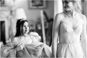 Flower girl holding bride's wedding gown