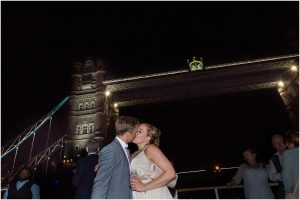 Bride and groom kiss under Tower Bridge at their wedding party on a London riverboat