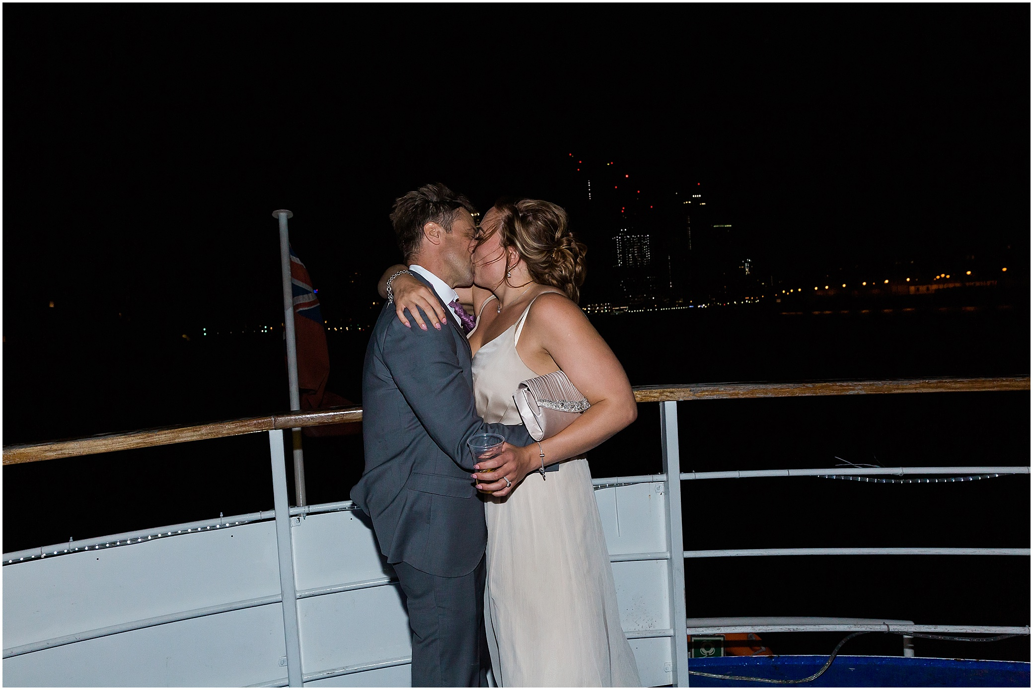 Bride and groom kiss at their wedding party on a London riverboat