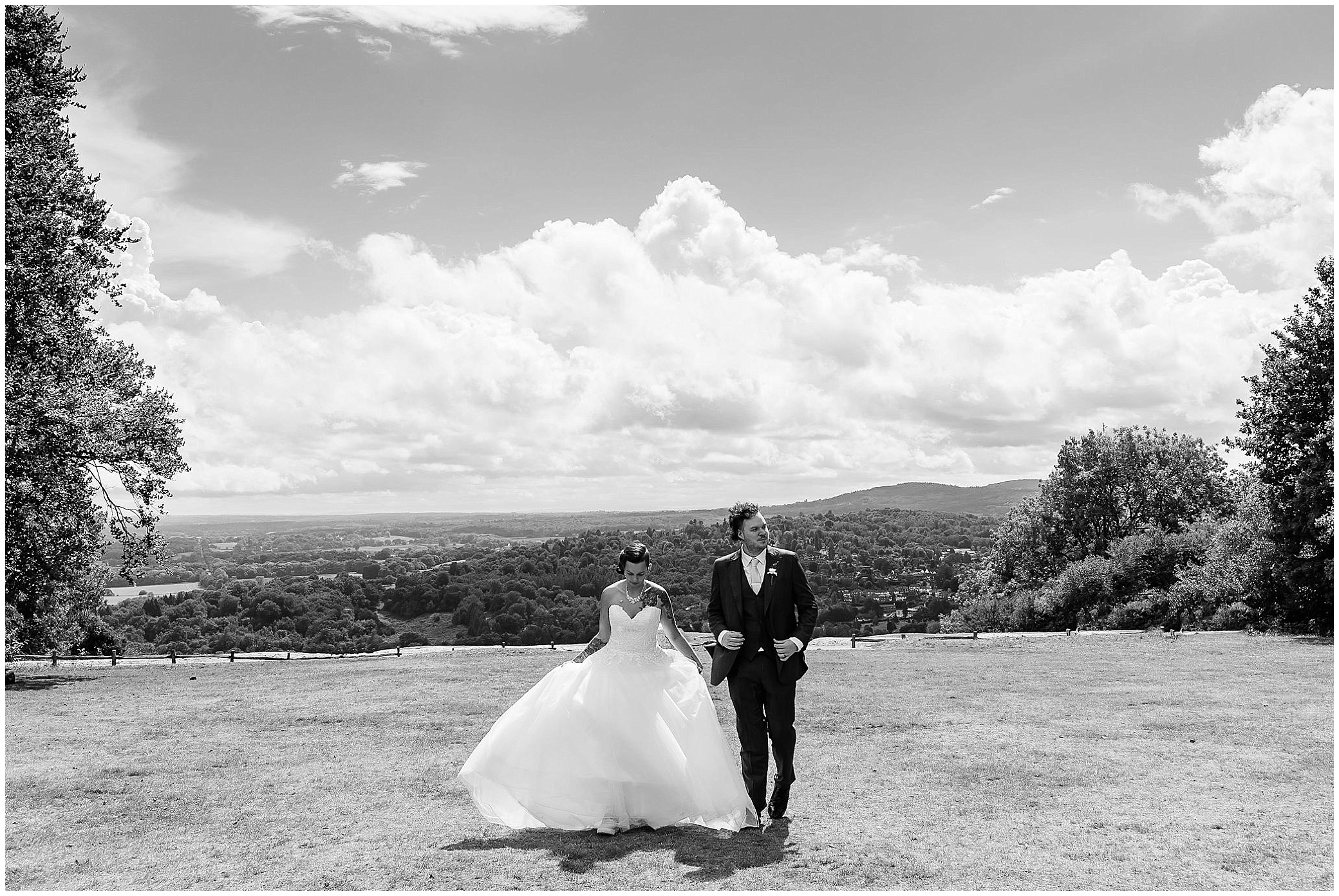 black and white image of a bride and groom walking on Boxhill in Surrey